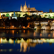 Prague Castle reflected on the Vltava River with the Charles Bridge at right