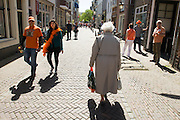 Een oudere vrouw loopt met langs de feestvierders tijdens Koninginnedag in Utrecht.<br />