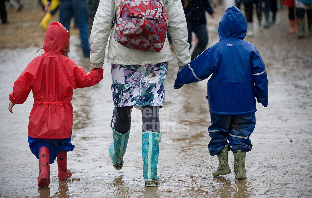 Picture by Daniel Hambury. .16/7/11..A young family walking in the mud and rain at Latitude, a music and arts festival set on the Henham Estate in Suffolk..The event runs from July 14th to 17th 2011.
