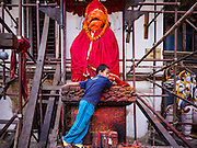 05 MARCH 2017 - KATHMANDU, NEPAL: A boy plays on a statue of Hunaman, the Hindu god depicted as a monkey, the statue is surrounded by scaffolding that is holding up the wall of the Hanuman Dhoka Palace on Durbar Square in Kathmandu, a UNESCO World Heritage Site badly damaged in the 2015 earthquake. Much of Kathmandu is now a construction site because of rebuilding  two years after the earthquake of 25 April 2015 that devastated Nepal. In some villages in the Kathmandu valley workers are working by hand to remove ruble and dig out destroyed buildings. About 9,000 people were killed and another 22,000 injured by the earthquake. The epicenter of the earthquake was east of the Gorka district.     PHOTO BY JACK KURTZ