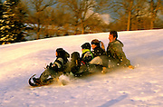 Family riding toboggan down fairway of Town and Country Golf course. St Paul Minnesota USA