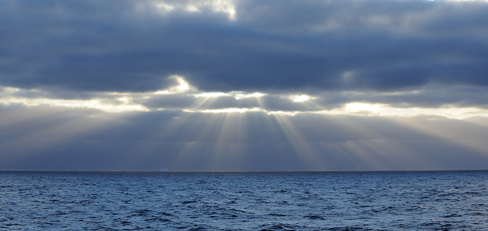Crepuscular rays appear as the sun breaks through broken cloud above the Southern Ocean near the South Orkney Islands. South Orkney Islands. 27Feb16