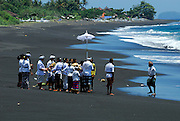 Hindu ceremony on black sand beach near Goa Lawah Temple, Bali, Indonesia.