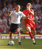 Photo: Henry Browne.<br /> Wales v England. FIFA World Cup Qualifying match.<br /> 03/09/2005.<br /> Luke Young of England holds off Sam Ricketts of Wales.