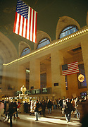 Main hall at Grand Central Station with sunlight coming in through windows and commuters rushing about. Large flags displayed after 9/11