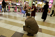businessman with mobile phone and paperwork at the entrance of a train station Tokyo Japan