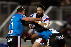Wakefield Trinity's Craig Huby is tackled by Salford Red Devils' Lama Tasi (right) and Josh Jones during the Betfred Super League match at Belle Vue Stadium, Salford.
