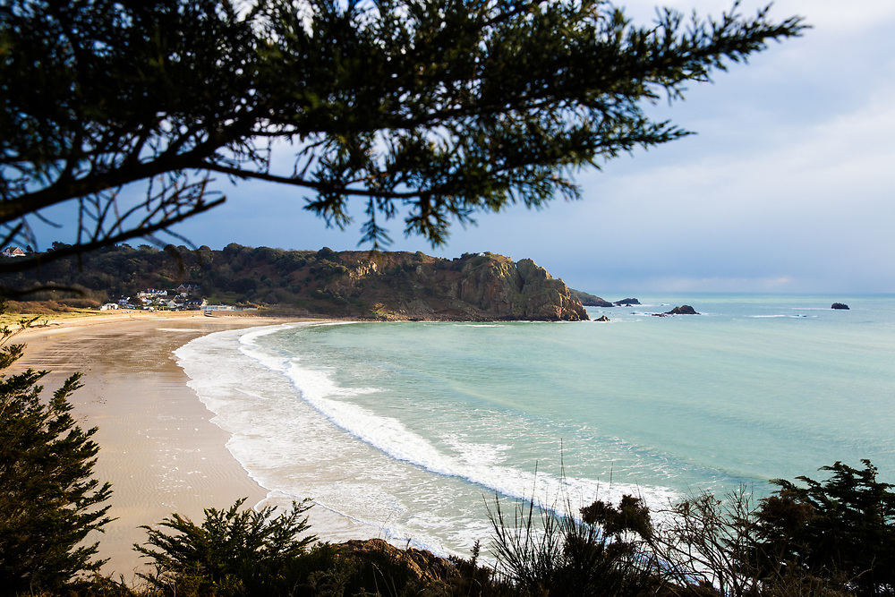 View of the calm sea and quiet beach through the trees at Ouaisne on a spring day in Jersey