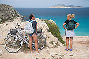 An Italian couple of holiday collect their bicycles after a morning at Cala Rossa bay on Favignana Island, Aegadian Islands (Isole Egadi), western Sicily, Italy