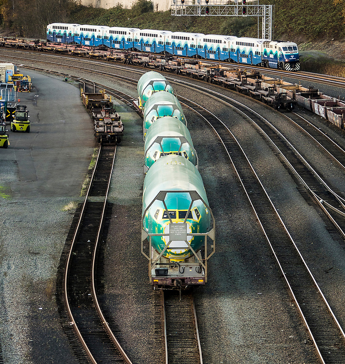 Boeing 737 fuselages on railroad cars near Seattle, Washington, for delivery by rail to the Boeing Renton Assembly Plant in Renton, Washington, US, 11/06/2018.  Above, a passing Sound Transit Sounder commuter train.