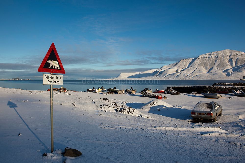 """Polar Bear Warning Sign on the outskirts of Longyearbyen, on the Arctic island of Spitsbergen, in Svalbard. There's more polar bears than people in the region, and it is dangerous to stray beyond the town limits without a gun, and knowing how to use it. The sign reads """"Gjelder hele Svalbard"""": """"the entire Svalbard""""."""