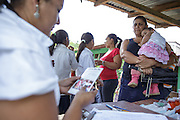 A woman holds her daughter as she waits to have her vaccinated during a vaccination session at the primary school in the town of Coyolito, Honduras on Wednesday April 24, 2013.