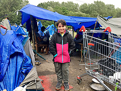 30July2021. Calais, France.<br /> A young Kurdish child inside the migrant refugee camp in Dunkerque. British founded charity Care4Calais along with other aid organisations offer food, assistance, phone charging, haircuts, clothing, tents and more to migrant refugees. A new 'Jungle' appears to be springing up from the trees and woods on the outskirts of Dunkerque where conditions are not as hostile or inhospitable as they are currently in Calais 30km to the south.<br /> Photo©; Charlie Varley/varleypix.com