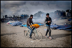 October 27, 2016 - Calais, Northern France, France - Image ©Licensed to i-Images Picture Agency. 27/10/2016. Calais, France. Calais Jungle Migrant Camp. Refugees walk past burning tents as they walk among the remains of  the migrant camp as Refugees leave the Calais Jungle migrant camp the day after it caught fire and the French police closed it down. Picture by Andrew Parsons / i-Images (Credit Image: © Andrew Parsons/i-Images via ZUMA Wire)