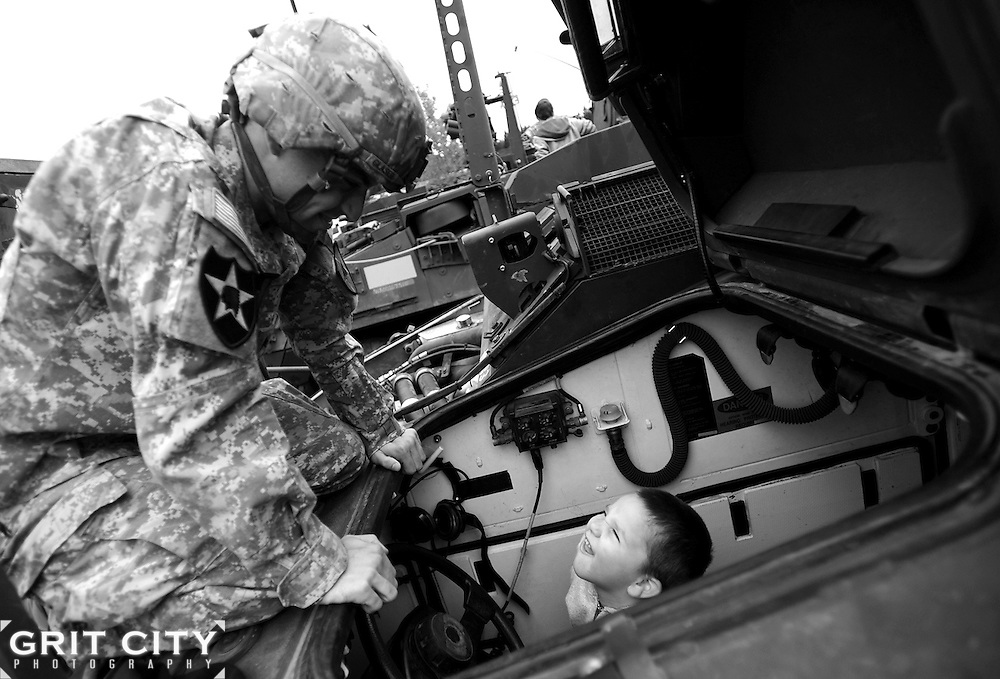 Sgt. Travis Glaser, 2-3 Inf., 3rd Bde., 2nd Inf. Div., gives Conor Canonico, 3, a tour of a Stryker vehicle on display Sept. 11 at the 8th Annual Military Family Support Day in Lacey.