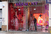 Worker checks the shop window of the adult store Harmony promoting Lilly Allens Womanizer on Oxford Street on 28th January 2021 in London, United Kingdom. Traditionally, this area of the West End has been the centre of the adult entertainment industry in London, UK with shops selling lingerie like this Harmony store.