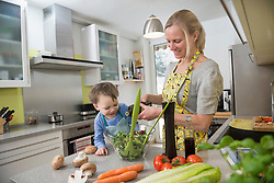Boy watching his mother while she flavors salad, smiling
