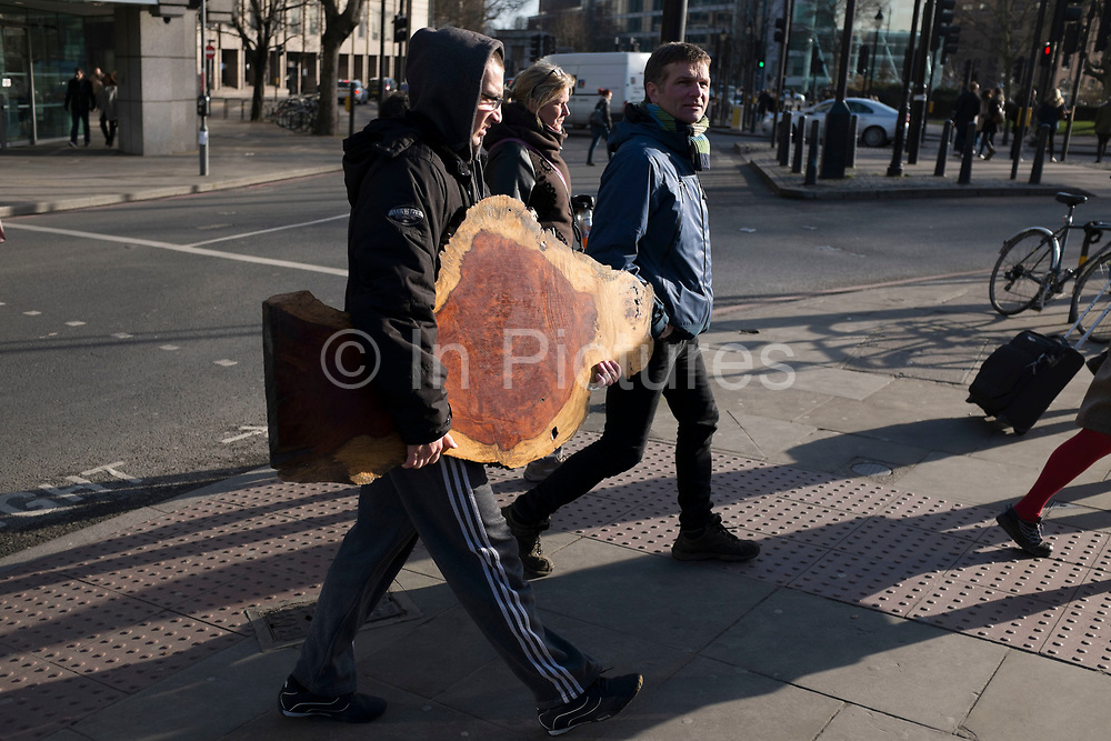 Man carrying a slice of wood from a treet trunk, London, UK.