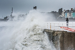© Licensed to London News Pictures. 28/11/2018. Aberystwyth, UK. Storm Diana, with winds gusting up to 60 or 70mph, combined with a high tide, bring huge waves battering the sea defences in Aberystwyth on the Cardigan Bay coast of west Wales. One man takes a risk in getting up close to the breaking waves on the promenade.The UK Met Office has issued a yellow warning for wind today and tomorrow for western part of the British Isles, with the risk of damage to property and likely disruption to travel .Photo credit: Keith Morris/LNP