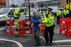 """© Licensed to London News Pictures. 27/10/2021. London, UK. A police officer removes a detailed person as protesters from climate campaign 'Insulate Britain', an offshoot of Extinction Rebellion (XR), block traffic on the A40 Western Avenue in Acton. Following a national injunction covering England's highways, Insulate Britain declared the M25 """"a site of nonviolent civil resistance"""" vowing to return to the motorway network to continue their protest action. Photo credit: Peter Manning/LNP"""