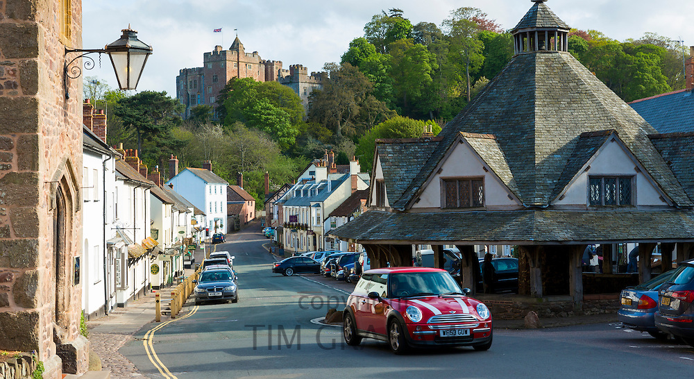 Motoring in a Mini car through the old medieval  town of Dunster in Somerset, United Kingdom