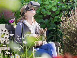 Girl using virtual reality headset while sitting on park bench with cat