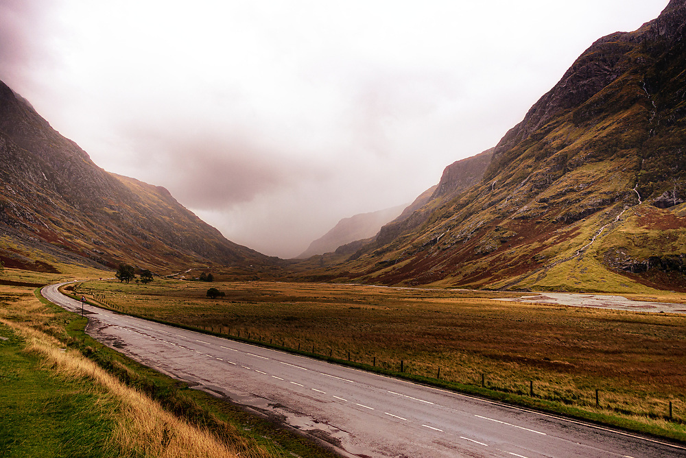 In sporadic rains, the hulking mountains of Glen Coe rise from the valley floor at the western end of the Glen