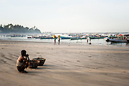 Myanmar, Ngapali. Man waits for his friends to come back from the sea.<br /> Every single morning all the fisherman from the little village at Ngapali Beach come back home with their night catch. At the beach all the women wait for them and afterwards work with drying and selling fish and other creatures from the sea begins.