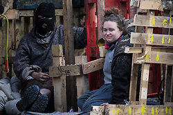 Denham, UK. 22nd March, 2021. Two anti-HS2 activists are pictured locked together during a large security operation by bailiffs from the National Eviction Team (NET) and Thames Valley Police to remove them and two other activists from a makeshift tower where they had been seeking to delay electricity pylon relocation works by Babcock in Denham Country Park.