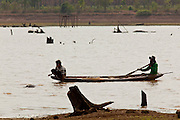 10 APRIL 2010 - NAKHON PHANOM, THAILAND: People try to fish in the bottom of Hua Hin Sanon reservoir in Nakhon Phanom province, Thailand. The reservoir is so low tree stumps left behind when it was opened are now surfacing. The 600 acre reservoir was built in 1985 and this the first year it's been empty. The region is in the midst of a record setting drought and the Mekong River is at its lowest point in nearly 50 years, setting up an environmental disaster the region has never seen before. Many of the people who live along the river farm and fish. They claim their crops yields are greatly reduced and that many days they return from fishing with empty nets. The river is so shallow now that fisherman who used to go out in boats now work from the banks and sandbars on foot or wade into the river. In addition to low river levels the Isan region of Thailand is also in the midst of a record drought and heat wave. Farmers have been encouraged to switch from rice to less water intensive crops and to expect lower yields. Farmers here rely more on rain fall than irrigation to water their crops.       PHOTO BY JACK KURTZ