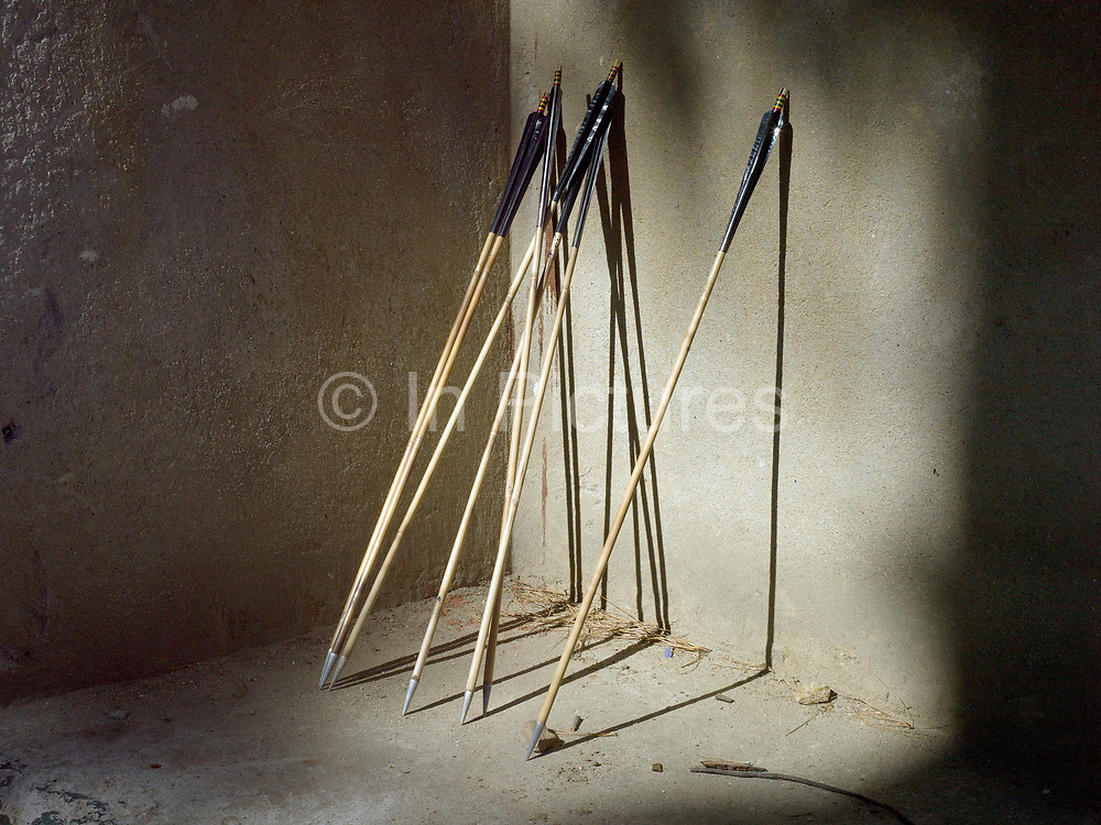 Arrows resting against a wall during an archery tournament in Thimphu, Western Bhutan. 'Datse' (archery) is Bhutan's national sport and is played wherever there is enough space and remains the favourite sport for men of all ages. There are archery tournaments held throughout the country. The targets are placed 140m apart. If the contestant hits his target, his team mates will perform a slow dance and sing his praises, while he slips a coloured scarf into his belt.
