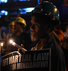 July 21, 2017 - Manila, Philippines - Workers joined by protesters from different groups light candles in front of the gates of the presidential palace in Manila on 21 July 2017. The protesters are on their 5th day of their camp-out protest as they continue to call for the end of labor contractualization and the lifting of martial law in Mindanao. (Credit Image: © George Calvelo/NurPhoto via ZUMA Press)