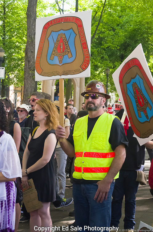 A union protestor in hard hat from the United Brotherhood of Carpenters and Joiners holds a sign at the 2015 May Day rally in Portland, Oregon.