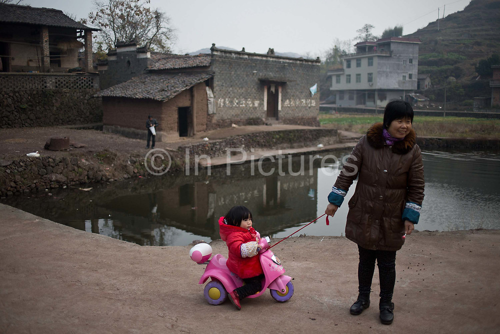 A young girl plays on her scooter at a rural village in Shangrao, Jiangxi Province, China on 12 December 2012.   The villages near the city of Shangrao are known for openly defying China's one child policy as most families have more than one child.