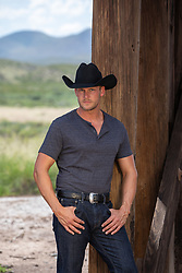 cowboy leaning against a large wooden post outdoors