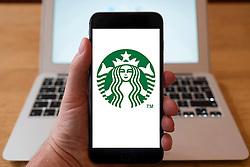 Using iPhone smartphone to display logo of Starbucks coffeeshop chain