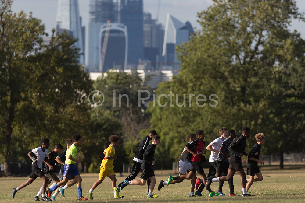 Youth football players warm up by running around part of Ruskin Park with the skyline of the City of Londons financial district, on 8th August 2018, in London, England.
