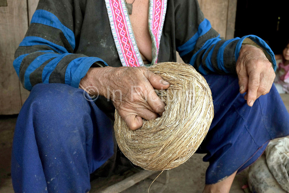 Wearing her traditional clothing, an elderly Hmong woman holds a ball of hemp fibre outside her home in Ban Chalern, Phongsaly province, Lao PDR. Making hemp fabric is a long and laborious process; the end result is a strong durable cloth with qualities similar to linen which the Hmong women use for their traditional clothing. In Lao PDR, hemp is now only cultivated in remote mountainous areas of the north. The remote and roadless village of Ban Chalern is situated along the Nam Ou river and will be relocated due to the construction of the Nam Ou Cascade Hydropower Project Dam 7.