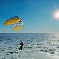 ANTARCTICA. Ski expedition member parasails in katabatic winds on vast polar icecap near Ellsworth Mountains, at 80 degrees south latitude.