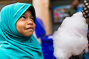 07 JULY 2013 - NARATHIWAT, NARATHIWAT, THAILAND: A Thai Muslim girl with cotton candy handed out by Royal Thai Marines Sunday. Royal Thai Marines in Narathiwat province held a special ceremony Sunday in advance of Ramadan. They presented widows, orphans and indigent people with extra rice and food as a part of the Thai government's outreach to resolve the Muslim insurgency that has wracked southern Thailand since 2004. The Holy Month of Ramadan starts on about July 9 this year. Muslims are expected to fast from dawn to dusk, engage in extra prayers, recitation of the Quran and perform extra acts of charity during Ramadan. It is the holiest month of the year for Muslims.    PHOTO BY JACK KURTZ