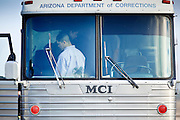 28 JANUARY 2010 -- BUCKEYE, AZ: An inmate waits at the front of the DoC bus to transfer to an ICE bus. The Arizona Department of Corrections transferred 51 undocumented immigrant inmates from state control to the Immigration and Customs Enforcement at Lewis Prison in Buckeye Thursday morning. The inmates have less than 90 days left on their sentences and will be deported to their countries of origin when they finish their prison terms.  PHOTO BY JACK KURTZ