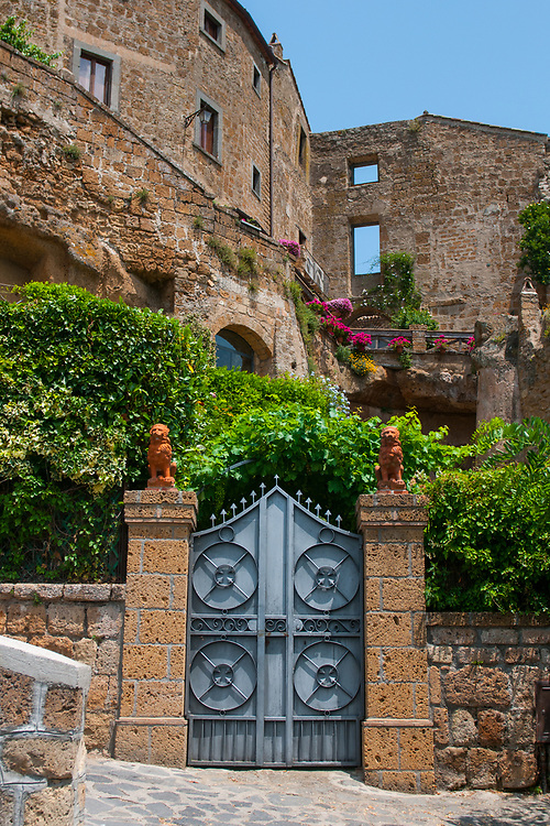 """An entrance along the climb to reach the village of Civita di Bagnoregio.<br /> Civita di Bagnoregio is a town in the Province of Viterbo in central Italy, a suburb of the comune of Bagnoregio, 1 kilometre (0.6 mi) east from it. It is about 120 kilometres (75 mi) north of Rome. Civita was founded by Etruscans more than 2,500 years ago. Bagnoregio continues as a small but prosperous town, while Civita became known in Italian as La città che muore (""""The Dying Town""""). Civita has only recently been experiencing a tourist revival. The population today varies from about 7 people in winter to more than 100 in summer.The town was placed on the World Monuments Fund's 2006 Watch List of the 100 Most Endangered Sites, because of threats it faces from erosion and unregulated tourism."""