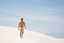 Nude muscular man walking on a sand dune in White Sands, NM