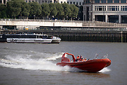 The Uber Boat 'Neptune Clipper' approaches the Canary Wharf pier and a  high-speed speedboat with the 'Thames Rockets' company crosses the river Thames, on 16th September 2021, in London, England.