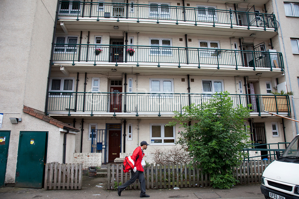 Postman delivers to council flats in Tower Hamlets, East London. Many people are at risk of losing their homes in London with the introduction of new benefit rules, which may push many people renting or who own council apartments out of the city. Tower Hamlets is a poor and over populated borough with many people living in small homes in high rise apartment blocks.
