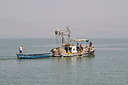fishing boat and dinghy rounding up fish in a net the Sea of Galilee, Israel
