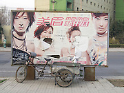 a dilapidated advertising billboard with a bicycle cart parked in front of it Beijing China