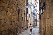 Young boy running through the alleyways of old town Hondarribia, in Basque Country, Spain
