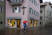 Cyclist carrying red umbrella walks towartds shop, under large town crucifix in Klausen-Chiusa in the Italian south Tyrol.