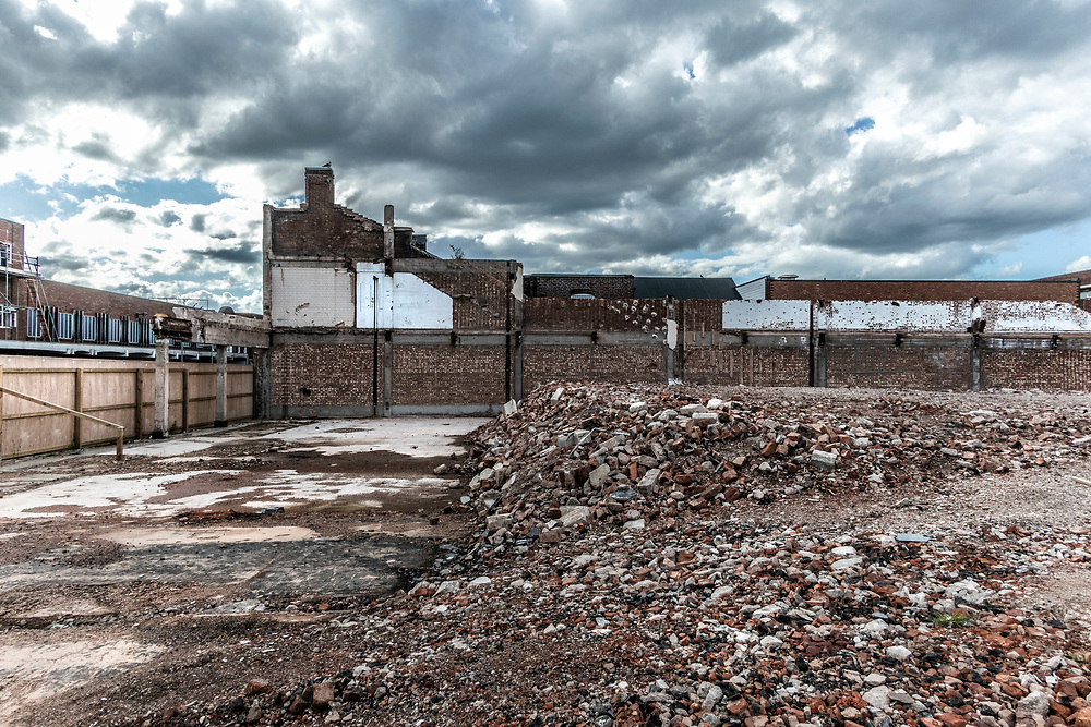 Piles of rubble sit behind the high street, waiting for redevelopment. West Bromwich, West Midlands, UK.